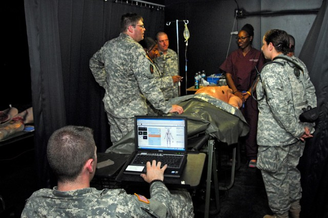 Soldiers assigned to Medical Command, New York Army National Guard, gather around Dr. Erica Igbindghene, an emergency room physician from Albany Medical Center, N.Y., as she outlines the  procedure for tracheal intubation, a medical term for insertion of a tube into an external or internal orifice of the body for the purpose of adding or removing fluids, during training at Camp Smith Training Site, Cortlandt Manor, N.Y., Aug. 5, 2014. Igbindghene was invited to attend a day of training with the New York Army National Guard medics during their annual training to help them  improve this skill. As she runs through the procedure, a MEDCOM Soldier uses a laptop computer to monitor the vital signs of the medical mannequin she is demonstrating with.