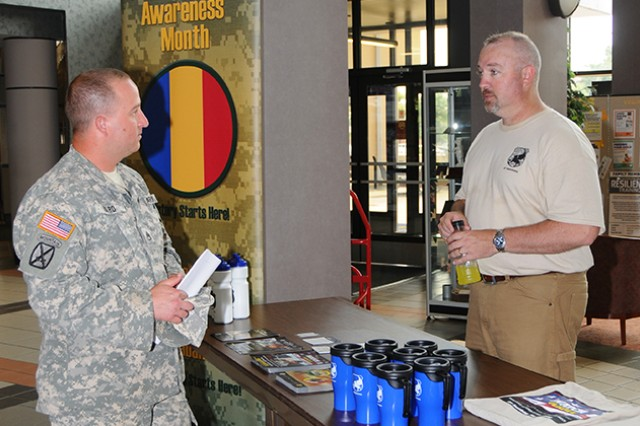 Cory Greenawalt, Fort Rucker TRADOC antiterrorism officer, discusses different aspects of antiterrorism prevention with Staff Sgt. Richmond Ward, 160th Military Police Battalion, in the atrium of Bldg. 5700 Aug. 8.