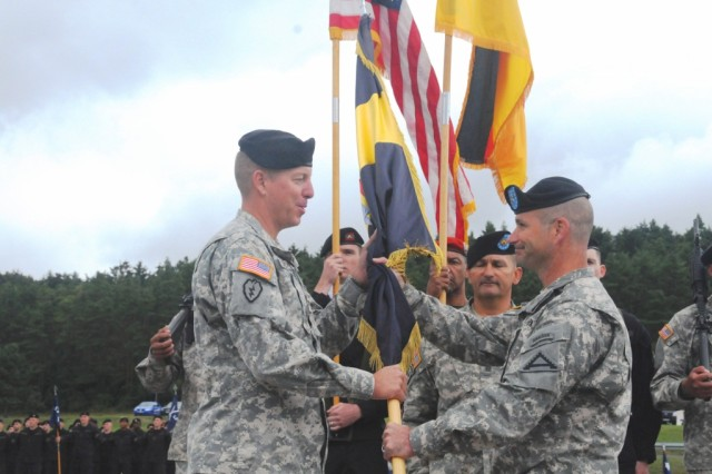Brig. Gen. Christopher G. Cavoli, (right) commander of the Joint Multinational Training Command, passes the guidon to incoming Joint Multinational Training Center commander, Col. Thomas H. Mackey, at an assumption of command ceremony at Hohenfels, Aug. 14.