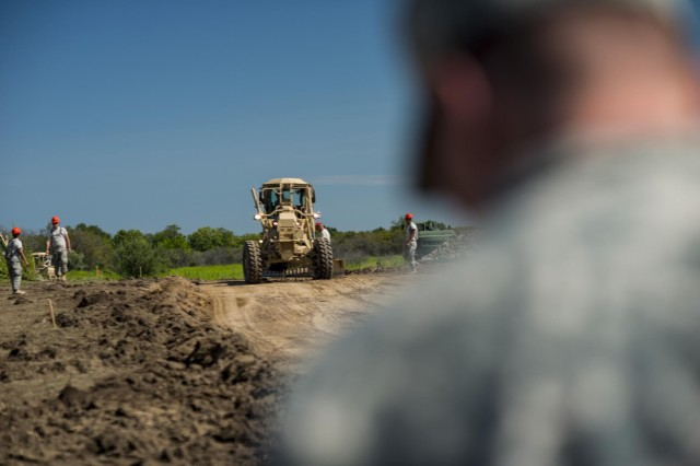 Engineers from the 317th Engineer Company use a motor grader to clear a dirt path and upgrade it to a rock-layered road at the Joliet Training Area in Elwood, Ill., to prepare the site for a Warrior Training Exercise scheduled for May 2015. The company used this work as an innovative readiness training opportunity to maintain and improve its engineer skills. The Joliet Training Area is the largest local training area run by the 88th Readiness Support Center in the Army Reserve. The 317th Eng. Company falls under the 416th Theater Engineer Command. (U.S. Army photo by Sgt. 1st Class Michel Sauret)