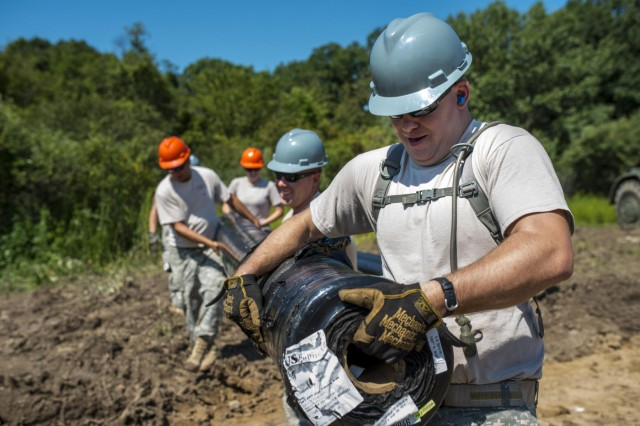 Engineers from the 317th Engineer Company carry a roll of geo fabric used for road construction at the Joliet Training Area in Elwood, Ill., to prepare the training site for a Warrior Training Exercise scheduled for May 2015. The company used this work as an innovative readiness training opportunity to maintain and improve its engineer skills. The Joliet Training Area is the largest local training area run by the 88th Readiness Support Center in the Army Reserve. The 317th Eng. Company falls under the 416th Theater Engineer Command. (U.S. Army photo by Sgt. 1st Class Michel Sauret)