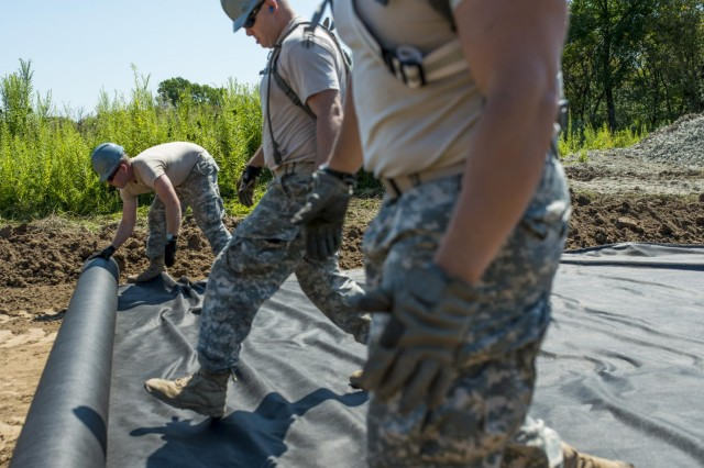Engineers from the 317th Engineer Company unravel a roll of geo fabric to improve a road at the Joliet Training Area in Elwood, Ill., to prepare the site for a Warrior Training Exercise scheduled for May 2015. The company used this work as an innovative readiness training opportunity to maintain and improve its engineer skills. The Joliet Training Area is the largest local training area run by the 88th Readiness Support Center in the Army Reserve. The 317th Eng. Company falls under the 416th Theater Engineer Command. (U.S. Army photo by Sgt. 1st Class Michel Sauret)