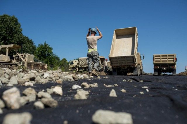 An engineer from the 317th Engineer Company backs up a truck (right) loaded with rocks to dump over the geo fabric material to improve a road at the Joliet Training Area in Elwood, Ill., to prepare the site for a Warrior Training Exercise scheduled for May 2015. The company used this work as an innovative readiness training opportunity to maintain and improve its engineer skills. The Joliet Training Area is the largest local training area run by the 88th Readiness Support Center in the Army Reserve. The 317th Eng. Company falls under the 416th Theater Engineer Command. (U.S. Army photo by Sgt. 1st Class Michel Sauret)