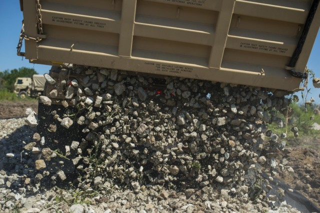 A load of 3-inch rocks dumps over a roll of geo fabric material to improve a road at the Joliet Training Area in Elwood, Illinois, to prepare the site for a Warrior Training Exercise scheduled for May 2015. The company used this work as an innovative readiness training opportunity to maintain and improve its engineer skills. The Joliet Training Area is the largest local training area run by the 88th Readiness Support Center in the Army Reserve. (U.S. Army photo by Sgt. 1st Class Michel Sauret)