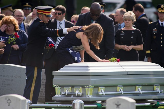 While son 1st Lt. Matthew Greene comforts his mother Dr. Susan Myers, she rests a rose on the casket of her husband, Maj. Gen. Harold J. Greene during his funeral at Arlington National Cemetery in Arlington, Va., Aug. 14, 2014. Greene is the highest-ranking U.S. military officer to be killed in combat since Vietnam.