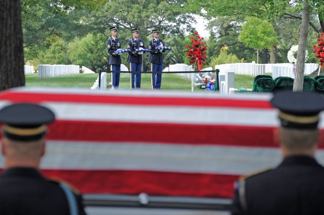 As the casket of Maj. Gen. Harold J. Greene prepares to be lifted from the caisson, three Old Guard Soldiers hold U.S. flags which will be presented to Greene's widow, son, daughter and father. Greene is the highest-ranking military officer to be killed in a combat zone since Vietnam.