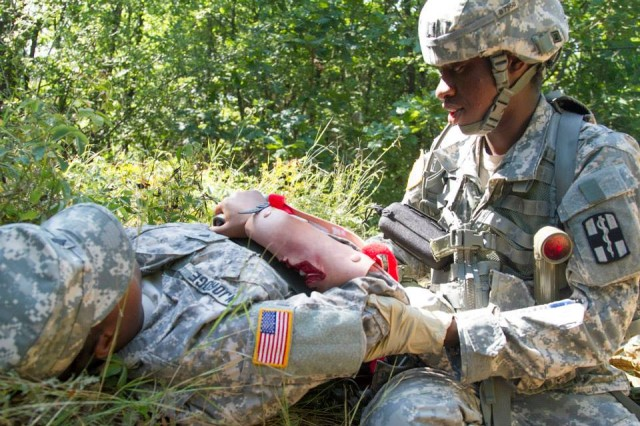 CAMP BONDSTEEL, Kosovo -- Capt. Ashley Bradley, a nurse with the 61st Multifunctional Medical Battalion, 1st Medical Brigade, treats a simulated casualty during a training exercise designed to prepare candidates for the Expert Field Medical Badge event in Grafenwoehr, Germany, Aug. 10.