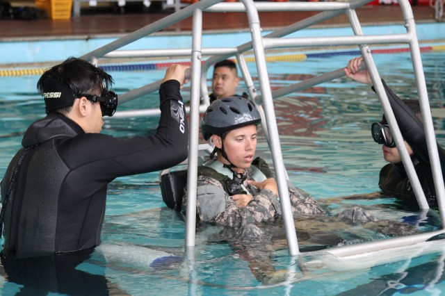 """POHANG, South Korea -- Pfc. Kayla L. Brinkerhoff, a UH-60 Black Hawk helicopter repairer and crew chief with Company B, 2nd Battalion (Assault), 2nd Aviation Regiment, 2nd Combat Aviation Brigade, 2nd Infantry Division, and native of Logan, Utah, prepares to be flipped upside down during a water survival course held at a Republic of Korea naval base in Pohang, South Korea, Aug.7.This training is essential to Brinkerhoff and her aviation counterparts here.""""With us, especially being on the peninsula, we are flying over water quiet frequently,"""" said Brinkerhoff. """"It's important we know what to do just in case something happens.""""Water survival training, also known as Dunker training, is given regularly to aviation Soldiers and is mandatory. (U.S. Army photo by Sgt. 1st Class Vincent Abril, 2nd CAB PAO)"""