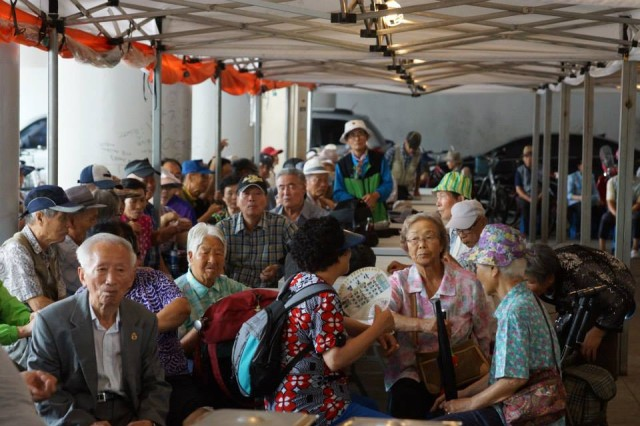 GANEUNG, South Korea -- Local citizens patiently wait on a meal as a liaison team from the 2nd Infantry Division, volunteer at the Ganeung soup kitchen, near Uijongbu, South Korea, July 25. (U.S. Army photo courtesy of Staff Sgt. Felix Mena/Released)