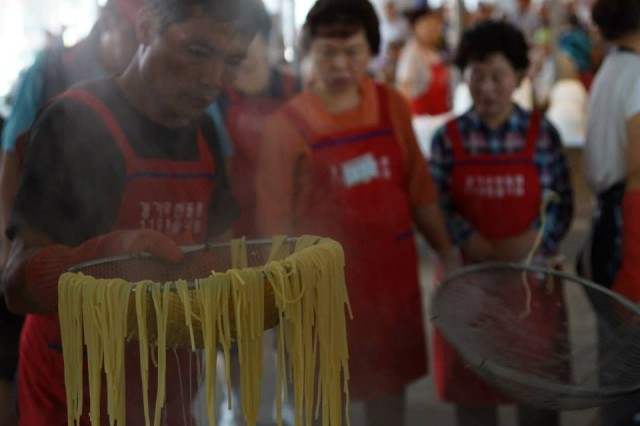 GANEUNG, South Korea --  A volunteer strains water from noodles in preparation for a meal at the Ganeung soup kitchen, near Uijongbu, South Korea, July 25. A liaison team from the 2nd Infantry Division volunteered at the soup kitchen. (U.S. Army photo courtesy of Staff Sgt. Felix Mena/Released)
