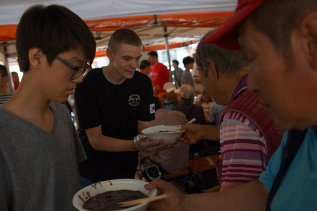 GANEUNG, South Korea -- Pfc. Jacob Ragle, a native of Marion, Ind., and a liaison assistant assigned to Headquarters and Headquarters Battery, 1st Batt. 38th FA Regt., 210th FA Bde., 2nd Inf. Div., and another volunteer serve soup to local citizens at the Ganeung soup kitchen, near Uijongbu, South Korea, July 25. (U.S. Army photo courtesy of Staff Sgt. Felix Mena/Released)