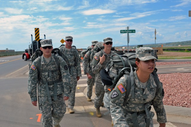 Soldiers from the 759th Military Police Battalion march from Butts Army Airfield to the Fort Carson Museum at Gate 1, after being transported by a UH-60 Black Hawk (MedEvac) from the 4th Combat Aviation Brigade, 4th Infantry Division, during 759th's MP competition on Fort Carson, Colo., Aug. 7, 2014.