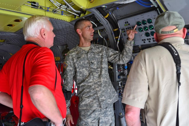 FORT CARSON, Colo. -- Staff Sgt. Jeremy Ganz, CH-47 Chinook flight engineer, 2nd General Support Aviation Battalion, 4th Aviation Regiment, 4th Combat Aviation Brigade, 4th Infantry Division, gives a tour of a CH-47F Chinook to Aviation Electrical Vietnam Veterans during their visit to 4th CAB hangars at Butts Army Airfield on Fort Carson, Colo., Aug. 7, 2014.    (Photo by Sgt. Jonathan C. Thibault, 4th Combat Aviation Brigade Public Affairs Office, 4th Infantry Division/Released)