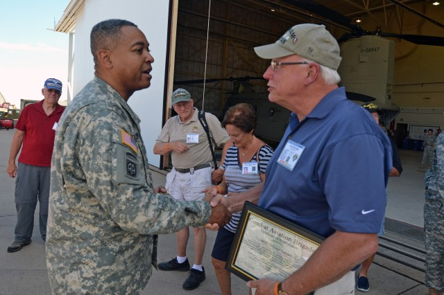 FORT CARSON, Colo. -- Command Sgt. Maj. Antoine Duchatelier, left, brigade command sergeant major, 4th Combat Aviation Brigade, 4th Infantry Division, presents a coin to Aviation Electrical Vietnam Veterans during their visit to 4th CAB hangars at Butts Army Airfield on Fort Carson, Colo., Aug. 7, 2014.    (Photo by Sgt. Jonathan C. Thibault, 4th Combat Aviation Brigade Public Affairs Office, 4th Infantry Division/Released)