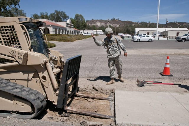 Spc. Orrin Duyssen, from Rochester, N.Y., guides the Bobcat in to lift and remove a section of sidewalk. The asphalt and concrete specialist with the 674th Engineer Detachment (Asphalt) is removing a sidewalk and paving it to connect the road and parking lot at a bus stop at Fort Hunter Liggett, Calif., during Castle Installation Related Construction Aug. 6 to 19. (U.S. Army photo by Staff Sgt. Debralee Best)