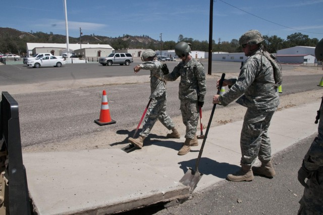 Soldiers with the 674th Engineer Detachment (Asphalt) remove a section of sidewalk  at a bus stop at Fort Hunter Liggett, Calif., during Castle Installation Related Construction Aug. 6 to 19. (U.S. Army photo by Staff Sgt. Debralee Best)