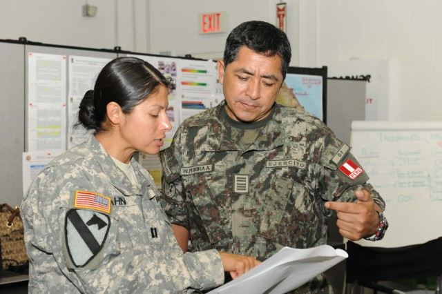 A U.S. Soldier talks with A Peruvian soldier Aug. 11 at the Coalition Forces Land Component Command headquarters during Fuerzas Aliadas- PANAMAX 2014 on Fort Sam Houston, Texas.  (U.S. Army photo by Robert R. Ramon, U.S. Army South Public Affairs)