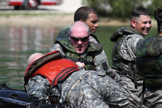 Sgt. Zachary Cunningham, an Ohio native, works to get Sgt. Matthew Hudson, Rogers, Arkansas, back into the Zodiac during boat drills conducted Aug. 14, 2014, by the Forward Support Company, 94th Engineer Battalion, 4th Maneuver Enhancement Brigade, 1st Infantry Division.