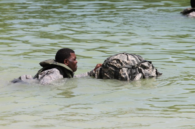 Staff Sgt. Brian Smith, a Dallas, Texas, native, swims with his waterproofed rucksack during a water operations training exercise conducted by the Forward Support Company, 94th Engineer Battalion, 4th Maneuver Enhancement Brigade, 1st Infantry Division, Aug. 14, 2014, at the Training Area 250 Lake, on Fort Leonard Wood, Mo.