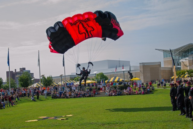 Sgt. 1st Class Aaron Figel, with the U.S. Army Special Operations Command parachute team, the Black Daggers, makes final adjustments for a tip-toe landing during a jump demonstration for National Airborne Day at the Airborne & Special Operations museum, in Fayetteville, N.C.