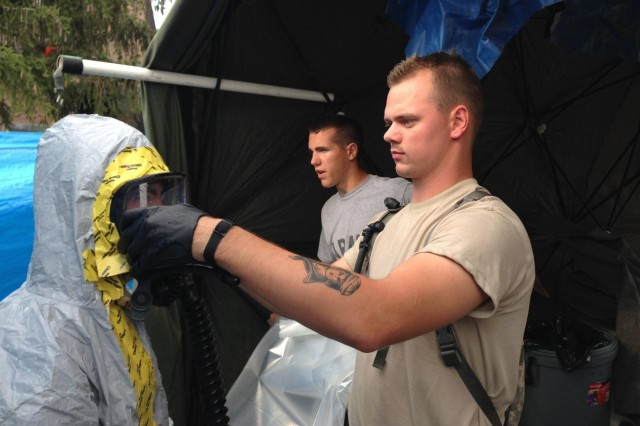 Spc. Zack Lemke assists a Soldier get mission ready by getting into a chemical suit during one of the chemical missions at Vibrant Response in Camp Atterbury, Ind., on Aug. 6. (U.S. Army photo by Spc. Matthew Ahlfs)