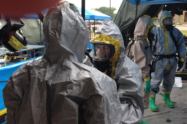 Two Soldiers from the 704th Chemical Company help get each other out of the chemical suits on a training mission at Camp Atterbury, Ind., during Operation Vibrant Response on Aug. 6. (U.S. Army photo by Spc. Matthew Ahlfs)