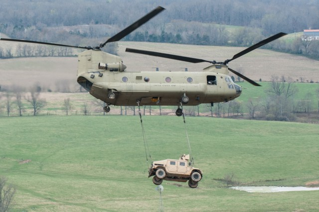 A CH-47 Chinook helicopter from B Company, 6th Battalion, 101st Combat Aviation Brigade, 101st Airborne Division (Air Assault), makes a turn while flying with a Humvee, during an air assault training mission, April 8, 2014, at Fort Campbell, Ky. The aircraft participated in Exercise Golden Eagle, a brigade-level air assault intended to update the Gold Book, the manual that covers air-assault operations in the Army.