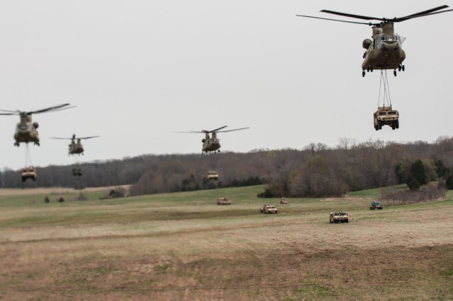 CH-47 Chinook helicopters from B Company, 6th Battalion, 101st Combat Aviation Brigade, 101st Airborne Division (Air Assault), sling load Humvees during an air assault training mission April 8, 2014, at Fort Campbell, Ky. The aircraft participated in Exercise Golden Eagle, a brigade-level air assault intended to update the Gold Book, the manual that covers air-assault operations in the Army.