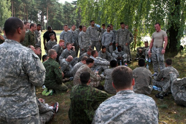 "Combatives Level III instructor Sgt. 1st Class Brett Macy of Indianapolis, mortar platoon sergeant for 1st Squadron, 91st Cavalry Regiment, 173rd Airborne Brigade, addresses ""Sky Soldiers"" and Lithuanian Land Forces ""Iron Wolf Brigade"" Soldiers at the completion of Combatives Level I certification Aug. 8. ""Sky Soldiers"" and ""Iron Wolves"" conducted combined training on Army Combatives Level I certification Aug. 4-8. The 173rd Airborne is currently deployed to Estonia, Latvia, Lithuania and Poland to demonstrate its commitment to NATO obligations and sustain interoperability with allied nations. (Photo by Staff Sgt. Scott Griffin, 207th Public Affairs Detachment)"