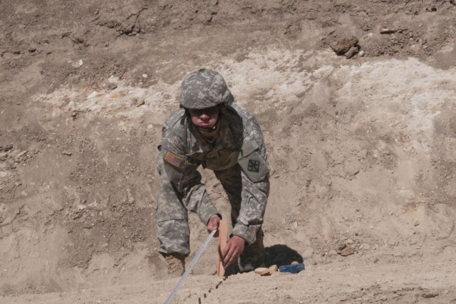 U.S. Army Reserve Pfc. John Curley, a technical engineer with the 476th Engineer Detachment, survey and design, from Marion Heights, Pa., checks the checks the distance between stakes to ensure accurate elevation point measurements for a project at Fort Hunter Liggett, Calif., at Castle Installation Related Construction, Aug. 6 to 19. (U.S. Army photo by Staff Sgt. Debralee Best)