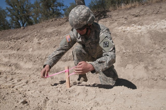 U.S. Army Reserve Pfc. John Curley, a technical engineer with the 476th Engineer Detachment, survey and design, from Marion Heights, Pa., ties pink engineer tape onto a stake to mark it for visibility while the detachment finds an elevation point for a project at Fort Hunter Liggett, Calif., at Castle Installation Related Construction, Aug. 6 to 19. (U.S. Army photo by Staff Sgt. Debralee Best)