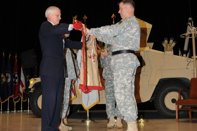 Ken Bousquet, ACC-Warren acting executive director, and Maj. Gen. Ted Harrison, ACC commanding general, uncase of the 923rd Contingency Contracting Battlation colors during the unit's activation ceremony.