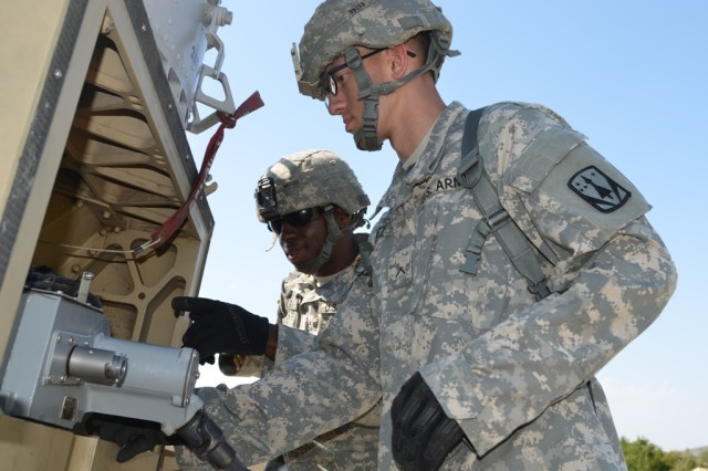 Cpl. Timothy Miller and Pvt. Christopher Vasquez perform ammunition loading on the land-based phalanx weapons system or LPWS during their mission readiness exercise on Fort Sill in August.