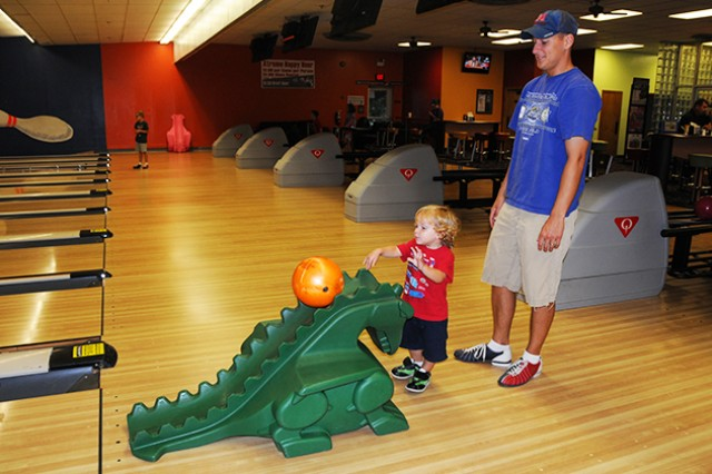 W01 Adam Nyitray, B Company, 1st Battalion, 145th Aviation Regiment, watches as his son, Kowen, bowls at Rucker Lanes Aug. 19.