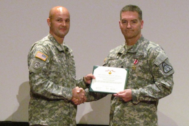 Lt. Col. Scott Anderson, right, is awarded the Meritorious Service Medal by Col. Courtney Cote during the Ground Maneuver Product Office change of charter ceremony.