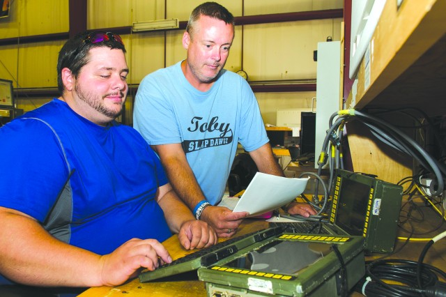 Electronics Mechanics Ian Haslam, left, and Kevin Yazdzik conduct electrical tests on the Secure Mobile Anti-Jam Reliable Tactical Terminal at Tobyhanna Army Depot.