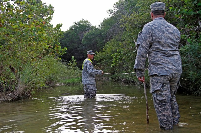 """Staff Sgt. Robert Owen (left) and Spc. Zachary Adkins, both combat engineers assigned to Headquarters and Headquarters Company """"Hammer,"""" 1st Brigade Combat Team """"Ironhorse,"""" 1st Cavalry Division, measure distance between two points in a stream to determine its velocity during First Team Training Aug. 21 at Fort Hood, Texas. The 1st Cavalry Division has emphasized the importance of continued professional development every Thursday during First Team Training. (U.S. Army photo by Spc. Paige Behringer, 1BCT PAO, 1st Cav. Div.)"""