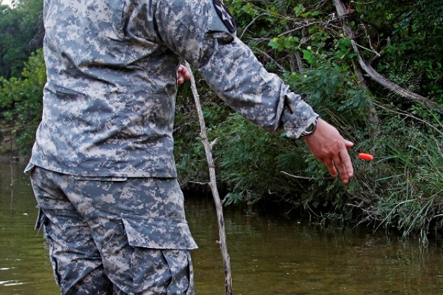 """Spc. Zachary Adkins, a Boscobel, Wisconsin, native and combat engineer assigned to Headquarters and Headquarters Company """"Hammer,"""" 1st Brigade Combat Team """"Ironhorse,"""" 1st Cavalry Division, drops a Styrofoam fishing float  into a stream while measuring its velocity during First Team Training Aug. 21 at Fort Hood, Texas. Adkins learned this aspect of his military occupational specialty in preparation for the upcoming multinational training exercise, Combined Resolve III. (U.S. Army photo by Spc. Paige Behringer, 1BCT PAO, 1st Cav. Div.)"""