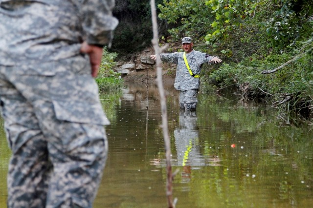 """Staff Sgt. Robert Owen (right), a Fort Worth, Texas, native and combat engineer assigned to Headquarters and Headquarters Company """"Hammer,"""" 1st Brigade Combat Team """"Ironhorse,"""" 1st Cavalry Division, explains measuring a stream's velocity during First Team Training Aug. 21 at Fort Hood, Texas. First Team Training includes a block of instruction and training activities as well as time designated for counseling Soldiers. (U.S. Army photo by Spc. Paige Behringer, 1BCT PAO, 1st Cav. Div.)"""