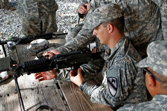 """Sgt. Daniel Felix (right) and Spc. Wesley Downs, both infantrymen assigned to Headquarters and Headquarters Company """"Hammer,"""" 1st Brigade Combat Team """"Ironhorse,"""" 1st Cavalry Division, review loading procedures of an M249 Squad Automatic Weapon during First Team Training Aug. 21 at Fort Hood, Texas. """"We have our junior leaders - this also includes junior officers - training Soldiers down to the small unit level with the intent of building their skill sets, but more importantly building a little bit of camaraderie as well as a more confident, resilient Soldier,"""" Capt. Michael Falls, commander of Hammer Company. (U.S. Army photo by Spc. Paige Behringer, 1BCT PAO, 1st Cav. Div.)"""