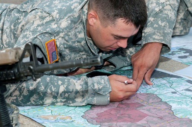 Spc. Fredrick Feliciano, a Port Reading, New Jersey, native and artilleryman with Battery C, 2nd Battalion, 82nd Field Artillery Regiment, 3rd Brigade Combat Team, 1st Cavalry Division, plots points on a map Aug. 18 at Fort Hood, Texas. Feliciano was given grid coordinates to plot and later find to complete the land navigation part of the best-by-test competition. (U.S. Army photo by Sgt. Brandon Banzhaf, 3rd BCT PAO, 1CD)