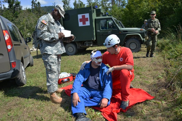 Sgt. 1st Class Ahmad Whitted, an observer/controller for exercise Immediate Response 14, observes the interaction between a role player and Slovenian Civilian Protection agent, during exercise Immediate Response 14, Aug. 25, 2014, in Postojna, Slovenia.