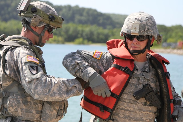Capt. Matvey Vikhrov (left), commander, 50th Multi-Role Bridge Company, 5th Engineer Battalion, 4th Maneuver Enhancement Brigade, 1st Infantry Division, assists Maj. Gen. Paul E. Funk II, commanding general, 1st Inf. Div. and Fort Riley, with his life vest just before they board a bridge erection boat to watch 50th MRBC bridge crews emplace a float raft, during the combined arms gap crossing exercise, Aug. 20, 2014, at Fort Leonard Wood, Mo. Funk joined Maj. Gen. Leslie Smith, commanding general, Maneuver Support Center of Excellence, and Col. Andy Munera, commander, 4th MEB, as the water operations commenced for the full-spectrum operation.
