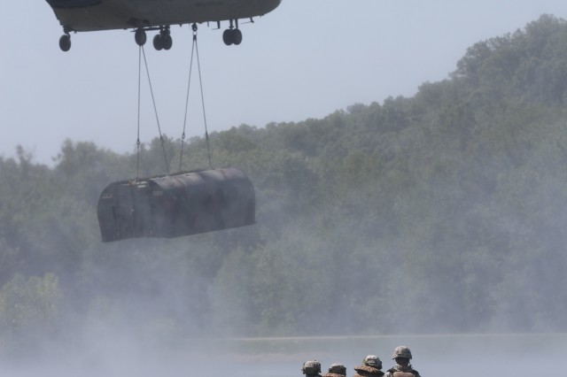 A bridging crew with 50th Multi-Role Bridge Company, 5th Engineer Battalion, 4th Maneuver Enhancement Brigade, 1st Infantry Division, wait as a CH-47 Chinook, with the 1st Combat Aviation Brigade, 1st Inf. Div., uses a sling-load method to lower a bridge bay during a combined arms gap crossing exercise, Aug. 20, 2014, at Fort Leonard Wood, Mo. Several units from 1st Inf. Div. provided Soldiers and equipment for the 4th MEB-led, full-spectrum operation.