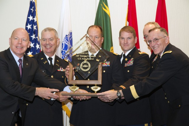 Brig. Gen. A. Ray Royalty, deputy commanding general, 108th Training Command (IET), and members of his team accept the top award for the Army Reserve from James Balocki, chief executive officer and director of Services and Installations for the United States Army Reserve, at the 2014 Army Communities of Excellence Awards. Five Army Reserve commands and 41 Army National Guard commands participated in this year's competition. The 81st Regional Support Command took runner-up for the Army Reserve while the Army National Guard's overall winner was the West Virginia National Guard.