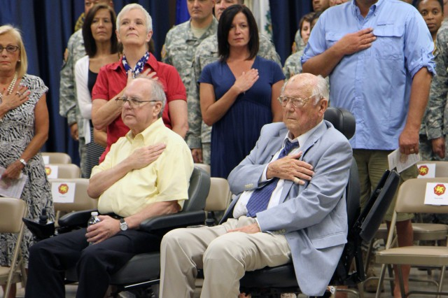 "Paul R. Hallman Sr., World War II Army-Air Force veteran and former P.O.W., along with his family and friends pay tribute to the American Flag during the playing of the national anthem at a ceremony in his honor. The ceremony held at the 108th Training Command (IET) Headquarters in Charlotte, N.C., Aug. 16, 2014, was one day shy of the 70th Anniversary of Hallman's 43rd combat flight during World War II. On that flight, Hallman, who served as an engineer on a B24J ""Liberator"", and his crew were shot down while performing a bombing mission over a Ploesti, Romania oil Refinery. Hallman and several other survivors of the flight were captured by German forces and held in Romania for several months until they were liberated by the Russian Army and returned to American forces later that year."