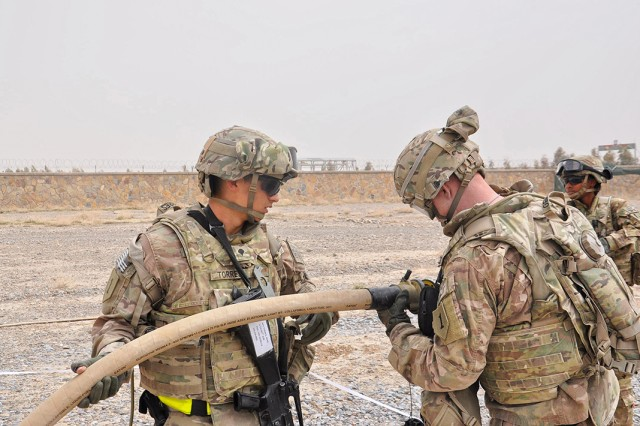 Spc. Rene Torres and Spc. Justin Gerdes connect two 50-foot fuel hoses while setting up a jump forward arming and refueling point using the Advanced Aviation Forward Area Refueling System at Camp Hero, Afghanistan.