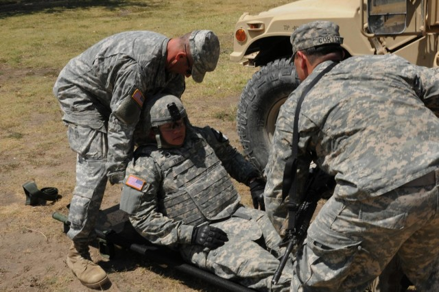 """First Lt. Mario Cortez Jr. (left), a platoon leader from San Antonio, and Sgt. 1st Class Jonathan Robbins, a platoon sergeant from Durham, Maine, both with Company A, 1st Squadron, 9th Cavalry Regiment """"Headhunters,"""" 2nd Brigade Combat Team, 1st Cavalry Division, prepare a simulated casualty for extraction during the medical evacuation event of the Headhunter leadership challenge, at Fort Hood, Texas, Aug. 15, 2014. The day-long competition was comprised of several events designed to build platoon leader-platoon sergeant relationships, and engage in healthy competition."""