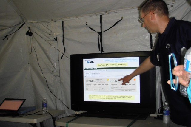 Ted Kline of the Penn State University Applied Research Laboratory, demonstrates to senior leaders how the fuel management system displays data, at Fort A.P. Hill, Va., June 13, 2014.