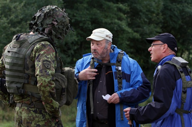 Estonian soldiers interact with civilians on the battlefield during an STX (simulated training exercise) lane at Hohenfels Training Area, Germany, Aug. 27, 2014. Saber Junction 14 is a large-scale, joint, multinational, annual military exercise, involving hundreds of aircraft and vehicles and thousands of personnel from 16 different nations. The exercise will prepare brigade-level units for worldwide contingency operations.  The exercise further focuses U.S., NATO, and partner forces on concepts such as decisive and sustainable land operations through the simultaneous combination of offensive, defensive and stability operations and on interoperability with partnered nations.